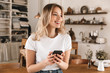 Portrait of pretty blond woman using smartphone while standing in stylish wooden kitchen at home
