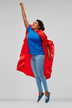 "Постер, картина, фотообои ""super power and people concept - happy african american young woman in superhero red cape flying up over grey background"""