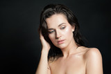 Attractive model woman with wet skin and hair on black background