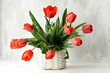 Quadro Bouquet of red tulips in a wicker vintage basket on a gray background.