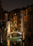 View into a small canal in Venice by night