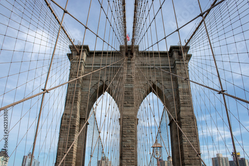 Fototapeten Brooklyn Bridge The famous Brooklyn Bridge Bridge located in New York City in the United States of America showing the suspension wired and the USA flag at the top of the column on a part cloudy day with blue Skys.