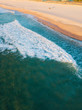 Leinwandbild Motiv Aerial view of empty beach with breaking wave on the coastline.
