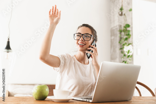 canvas print picture Student girl with apple sitting indoors using laptop computer talking by mobile phone.