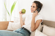 canvas print picture - Beautiful happy young student girl sitting indoors eat apple talking mobile phone on sofa.