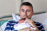 Happy man holding his newborn baby at the hospital. Life and family concept - 262240715