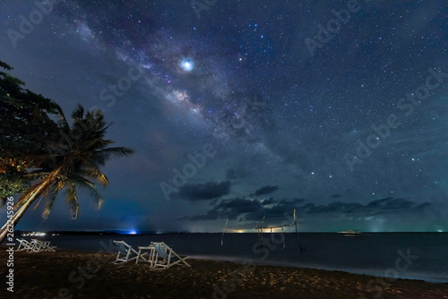The Milky Way rises above the sea by the beach at night.