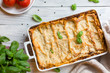 Homemade baked lasagna emiliane made from traditional meat ragù cooked for 4 hours, béchamel sauce, flat pasta. Served in a casserole  and cut into single-serving square portions. Top view.  - 262248163