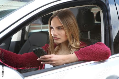 canvas print picture Junge Frau mit Handy am Steuer