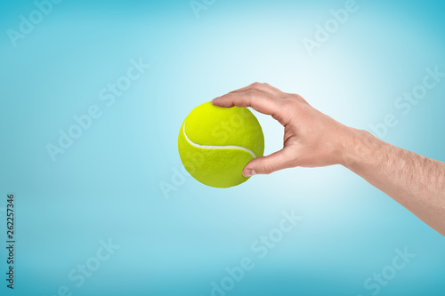 Male hand holding small tennis ball between fingers on blue background