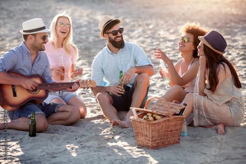 Leinwandbild Motiv Group of joyful friends on the beach