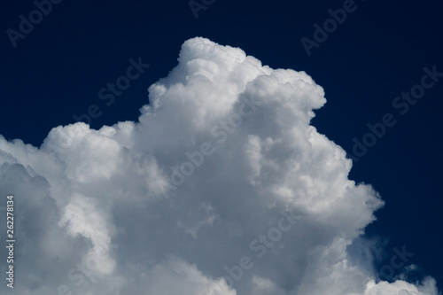 White cotton clouds on a dark blue sky - 262278134