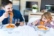 Handsome young father and her beautiful having fun while eating pasta with tomatoe sauce for lunch in the kitchen at home.