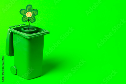Green trash can with flowers on a green background - 262322190