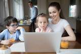 Mother showing cartoon on computer for children while father cooking