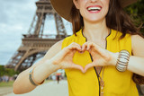 Closeup on happy traveller woman showing heart shaped hands