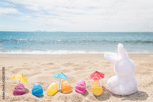 Beach Easter background with bunny and color eggs