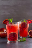 Blood orange cocktail with slices of citrus fruits and mint