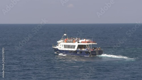 Tourboat off coast of Oia in Santorini, Greece, Europe