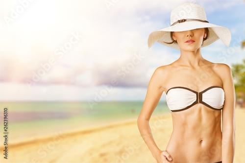 Leinwanddruck Bild Beautiful woman in blue swimsuit on tropic sea background