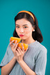 Quadro Healthy food. Smiling lovely pinup asian girl holding orange over blue background.