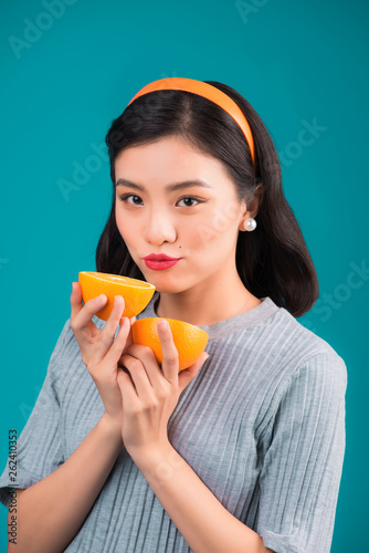 canvas print picture Healthy food. Smiling lovely pinup asian girl holding orange over blue background.