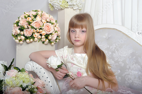 canvas print picture blonde young princess sits in a white smart dress on the couch among the flowers
