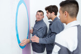 man showing apprentices how to paint a wall