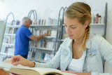young student woman reading a book in library