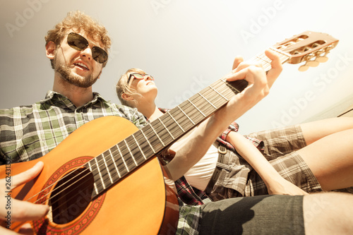 Young man hipster playing guitar for woman. - 262431332