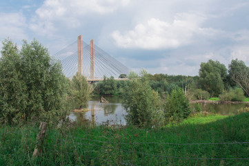 orange suspension, wire bridge Zaltbommel, called Martinus Nijhoff brug, The Netherlands. with trees and ditch