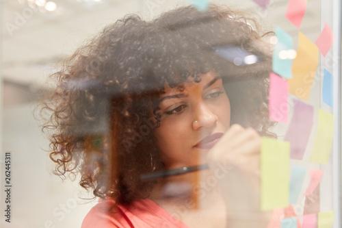Junge Business Frau schreibt Ideen auf Haftnotizen © Robert Kneschke