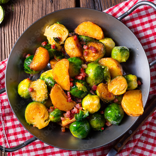 canvas print picture Brussels sprouts potato pan with bacon in rustic style