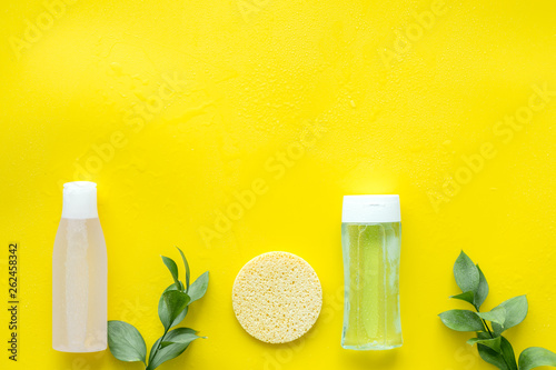 Leinwandbild Motiv mycelial water , lotion and sponge for skin care and plant on yellow background flat lay space for text