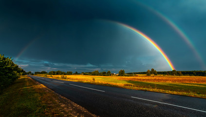 Double rainbow over the highway in darkly blue sky after a rain