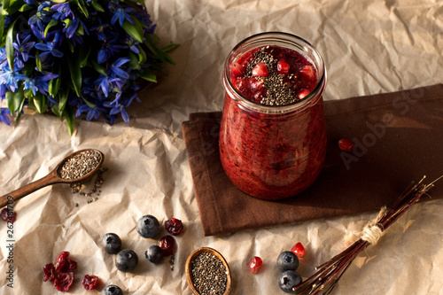 Organic smoothies with berries. Blueberry, cranberries. Red. Vitamin. Diet. Chia seeds. Flowers. Homemade. Sun light. Artichoke. Shadows. Nature. Wooden spoon. Garnet. © Igor