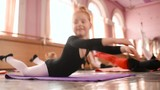 child little red-haired girl ballerina stretching and doing exercises in ballet school
