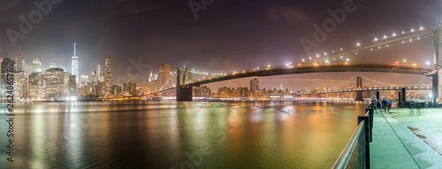 A panorama of the Brooklyn Bridge at night with the New York City skyline in the background. The East River is in front and parts of the Manhattan Bridge can be seen. - 262486578