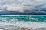 coast of the Atlantic Ocean during a storm, a white motor yacht on the horizon,