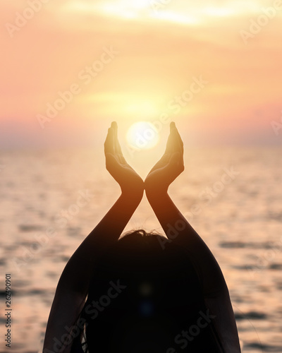 Leinwandbild Motiv June summer sun solstice concept with silhouette of happy young woman's hands relaxing, meditating and holding sunset against warm golden hour sky on the beach with natural ocean or sea background