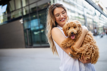 Beauty woman with her dog playing outdoors