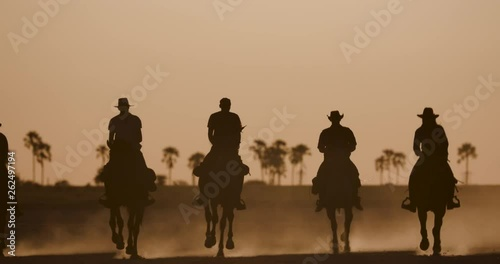 Spectacular view of a Group of horse riders riding at sunset on the Makgadikgadi salt Pans while the horses hooves kick up dust