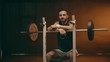Sportsman sitting near barbell, laughing and looking at camera
