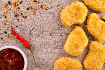 Chicken nuggets with a red hot chili pepper and a bowl of sauce on a concrete texture background. Directly above.