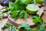 Lime, mint and cilantro -  green food ingredients on the wooden board.