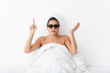 "Постер, картина, фотообои ""Woman with towel on head lies in bed covering body under blanket isolated over white wall background wearing sunglasses pointing."""
