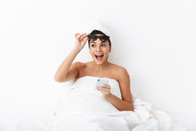 "Постер, картина, фотообои ""Beautiful surprised emotional woman with towel on head lies in bed under blanket isolated over white wall background wearing sunglasses chatting by phone."""