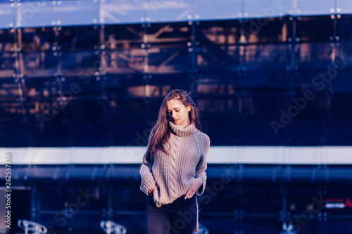 Gorgeous female in dressed in casual look standing outdoors near copy space area for advertising,