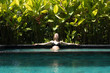 Quadro Sensual young woman relaxing in outdoor spa infinity swimming pool surrounded with lush tropical greenery of Ubud, Bali. Wellness, natural beauty and body care concept.