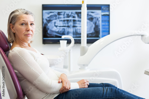 canvas print picture Cute mature woman sitting in dental chair